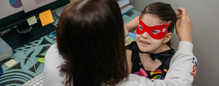 Woman teleworking and putting costume mask on her daughter