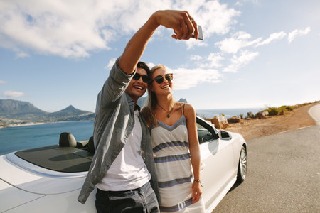 Couple standing by their car taking selfies