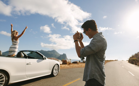 Man photographing his girlfriend in a cabriolet