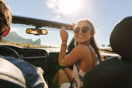 Woman traveling in a convertible car