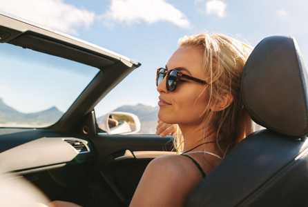 Woman on road trip in convertible car