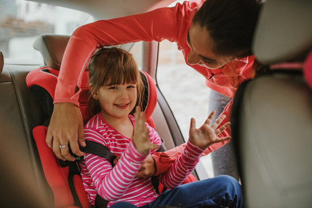 Woman buckling up on child in car safety seat