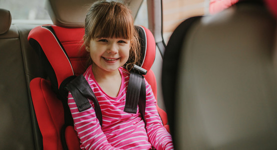 Cute girl buckled into her car seat