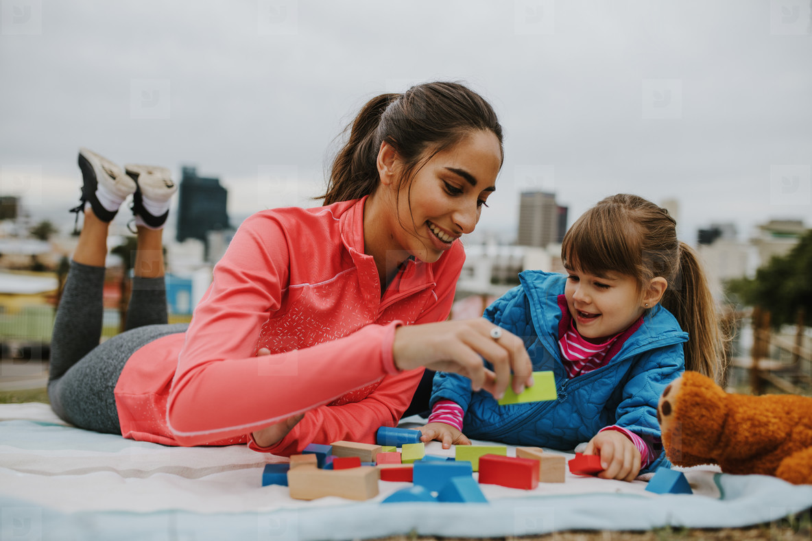 Girl and nanny playing wooden blocks