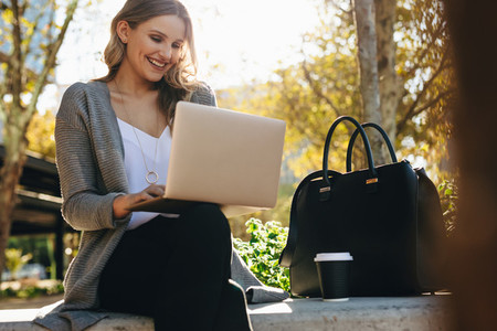 Businesswoman sitting outside using laptop