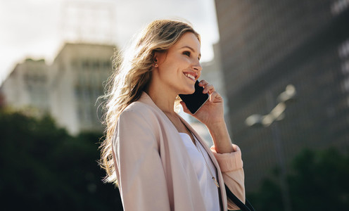 Businesswoman using cell phone walking outside