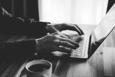 A man is typing on a laptop keyboard  Concept of work from home  black and white photo