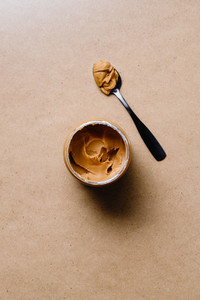 Opened peanut butter with black spoon  Shelf vegetarian food concept  Minimal style photography