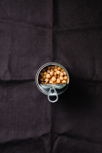 Opened can of chickpeas on a dark background  Shelf vegetarian food concept  Minimal style photography