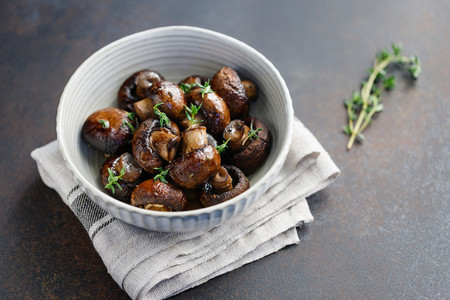 Roasted champignons with thyme in a ceramic bowl Simple taste recipe