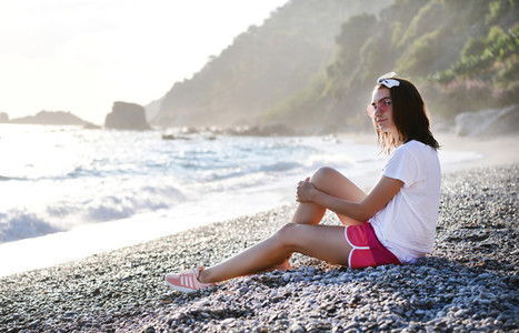 Young woman smiling at pebble beach at Mediterranean sea