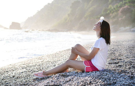 Young woman sitting at pebble beach at Mediterranean sea