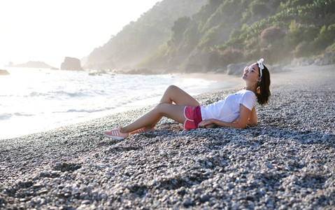 Woman lying and relaxing at beach at Mediterranean sea