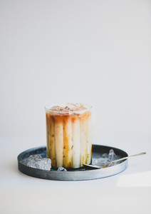 Iced caramel macchiato coffee with vanilla syrup in glass