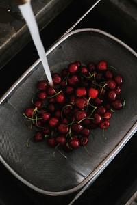 Fresh garden cherries being washed in strainer top view