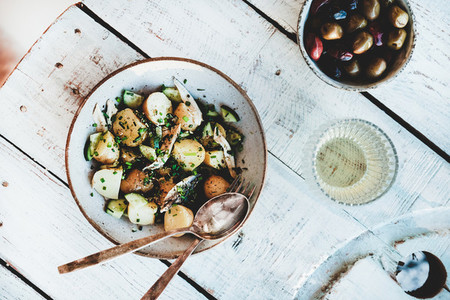 Healthy summer lunch with potato salad olives and white wine