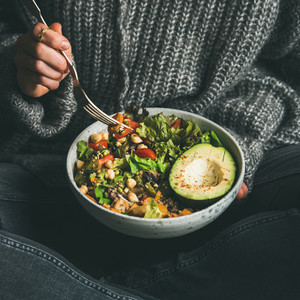 Woman eating fresh salad avocado beans and vegetables square crop