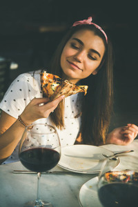 Happy caucasian woman eating pizza and drinking wine