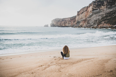 Woman sitting at Atlantic ocean beach in Portugal