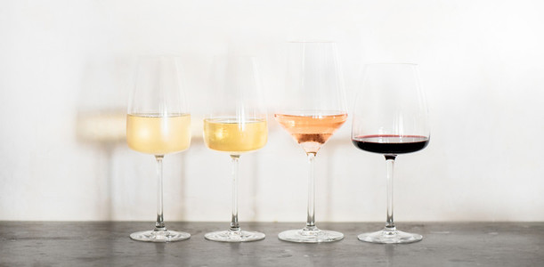 Variety of wine types over concrete table  wide composition