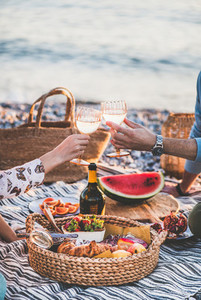 Couple having picnic at seaside and clinking glasses with wine