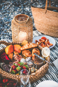 Summer picnic concept with tasty appetizers fruits and croissants