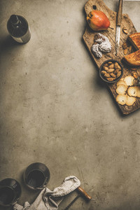 Glasses of red wine  wine bottle  snacks on wooden board