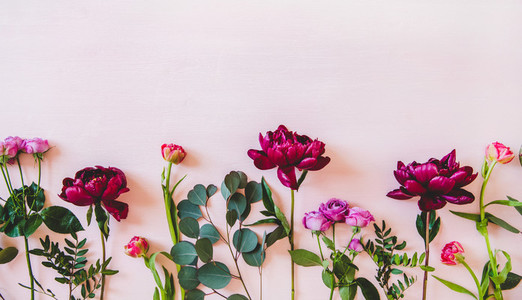 Summer flowers and branches flat lay over pink background copy space