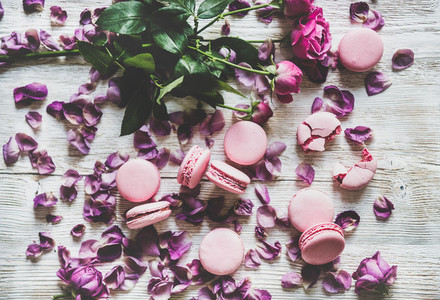 Sweet pink macaron cookies and rose flowers and petals