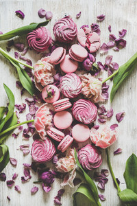Sweet pink macarons marshmallows and spring flowers on wooden background