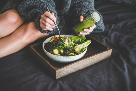 Healthy vegan bowl on tray and woman eating