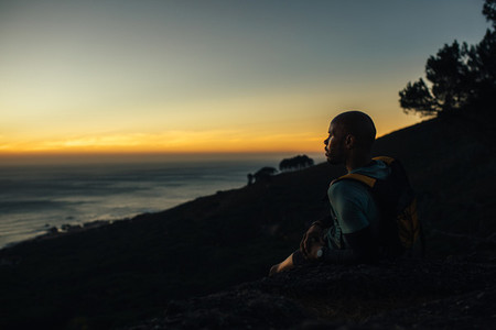 Sportsman resting by mountain trail at sunset