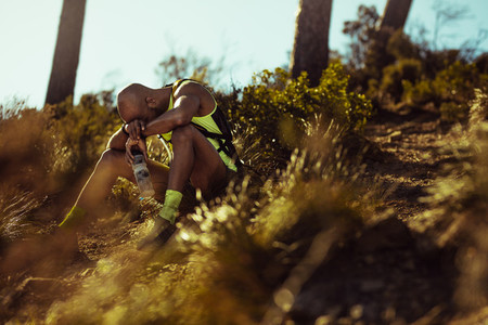 Runner looking tired taking rest on mountain trail