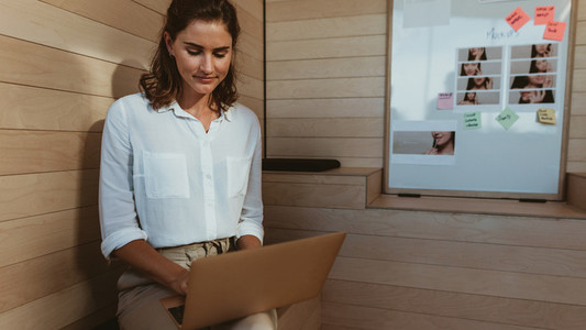 Businesswoman working on laptop in creative office