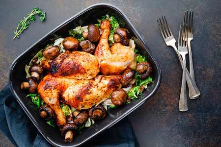 Top view of roasted chicken legs and breasts with fresh salad and mushrooms in black dish