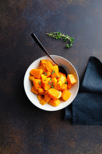 Roasted pumpkin pieces with fresh thyme in a ceramic bowl on a table  Seasonal Autumn recipe