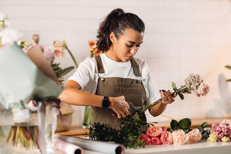Woman florist cutting flowers
