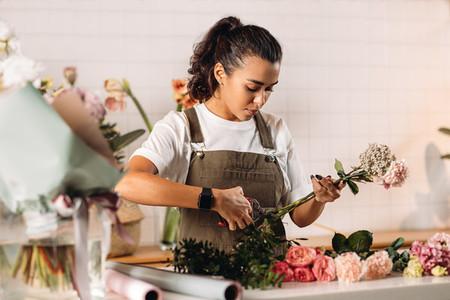 Woman florist cutting flowers