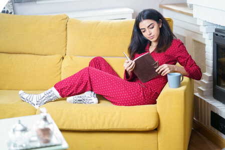 Woman at home having tea and reading