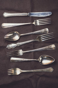 Metal vintage cutlery on a dark linen napkin in a row Flat lay top view