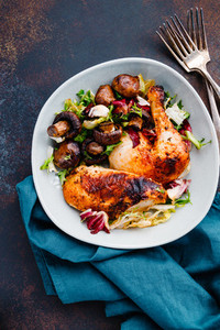 Roasted chicken leg and breast with fresh salad and champignons on a plate