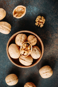 Top view oo walnuts in a wooden bowl on a table