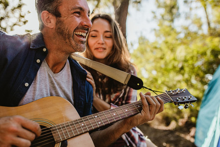 Man playing music with girlfriend at campsite