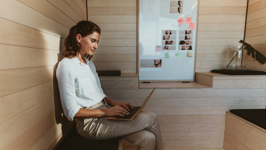 Businesswoman sitting in creative office working on laptop