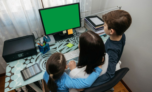 Mother and children looking at computer screen
