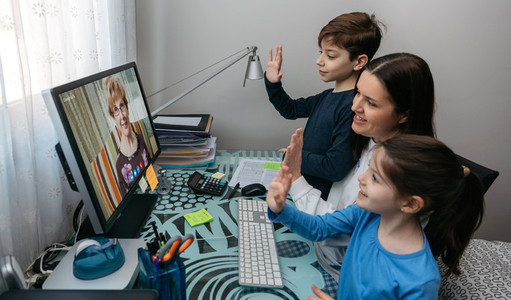 Family waving on video call with grandmother