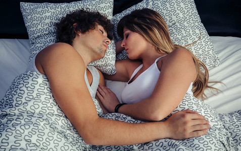 Couple sleeping embraced in bed