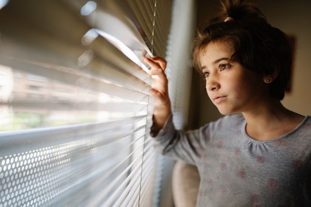Nine years old girl looking out the window through the blinds