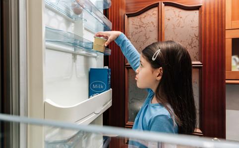Sad girl taking the last yogurt from the fridge