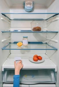 Girl hand taking the last yogurt from the fridge